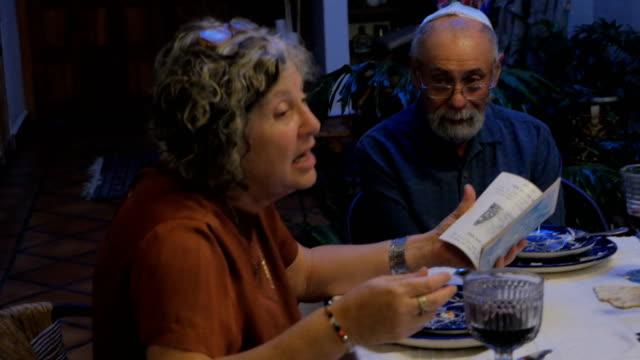 vídeos y material grabado en eventos de stock de una mujer judía cuenta una historia de un libro en una mesa - pascua judía