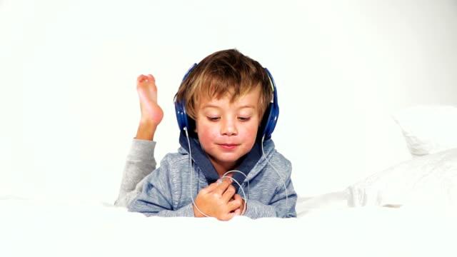 4 jähriger バブ im bett mit kopfhörern spielt mit dem タブレット ビデオ
