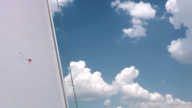 Jib and clouds Calm sunny weather. Red thread - wind sensor on the sail. Active contrasting clouds in the sky. canvas fabric stock videos & royalty-free footage