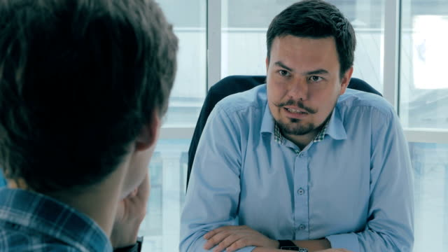 Job interview. Manager, boss in office talking with an applicant. Over the shoulder view video