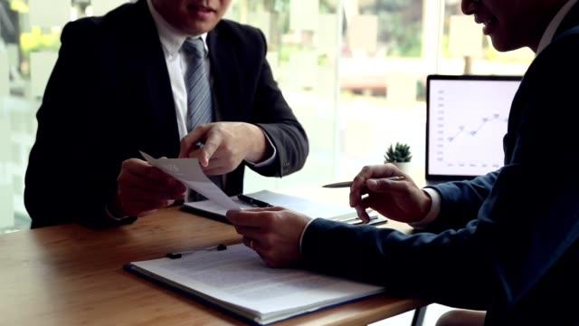 berufsbefragte verweisen auf den lebenslauf im mitarbeiter-lebenslaufdokument und sprechen über die berufserfahrung des mitarbeiters. - feedback stock-videos und b-roll-filmmaterial