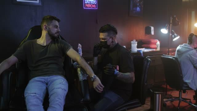 job profession work with man drawing tattoo in beauty studio - tatuaż filmów i materiałów b-roll