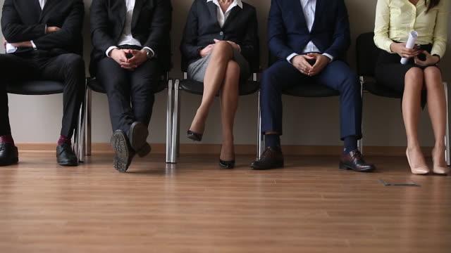 면접을 기다리는 대기열에 앉아 있는 실업 지원자 그룹 - unemployment 스톡 비디오 및 b-롤 화면