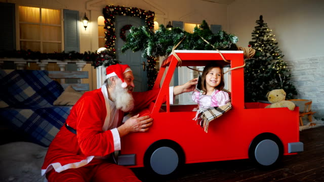 Jocund Father Christmas asking girl to talk by phone video