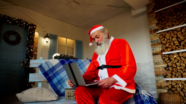 Jocund Father Christmas talking with video by laptop video