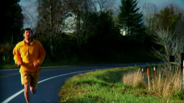 jogger country road dolly left medium shot hd - bir orta yetişkin erkek sadece stok videoları ve detay görüntü çekimi