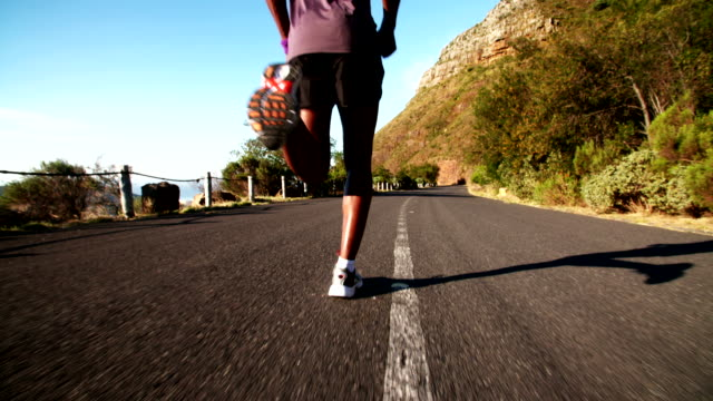 Jogger running along mountain road in slow motion Jogger running along mountain road in slow motion black people stock videos & royalty-free footage