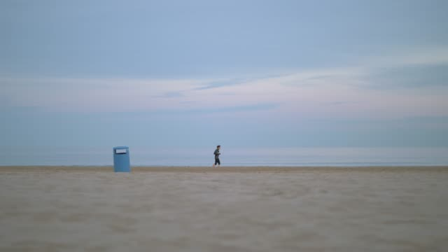 Jogger running beside the sea on a cold day