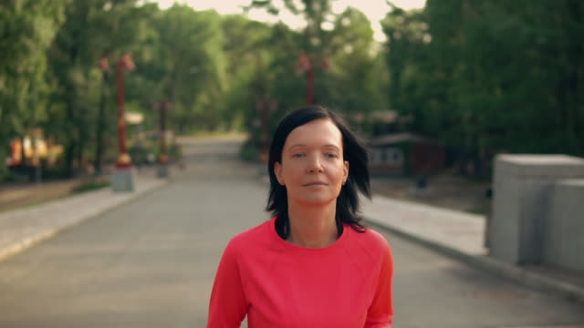 jogger runs in park slow motion portrait young woman running outdoors. caucasian girl with black hair wearing red sportswear sleeve stock videos & royalty-free footage