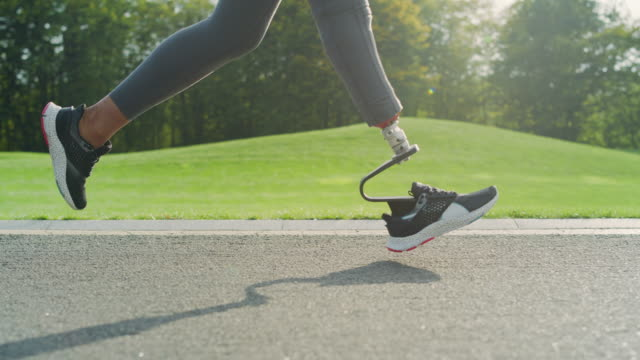 Jogger with artificial limb doing cardio on road. Athlete running outdoors Low view sporty jogger with artificial limb doing cardio workout on road. Close up runner woman legs exercising in park. Energetic athlete feet running outdoors in slow motion artificial limb stock videos & royalty-free footage