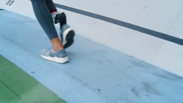Jogger with artificial limb exercising at stadium. Girl doing cardio outdoors Low section jogger with artificial limb exercising at stadium track. Disabled runner woman legs running on racetrack. Sporty girl with prosthetic leg doing cardio outdoors in slow motion artificial limb stock videos & royalty-free footage