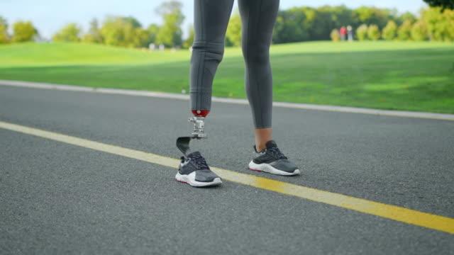 vídeos y material grabado en eventos de stock de jogger con extremidad artificial de pie en el parque. mujer en posición de salida en carretera - columna vertebral humana