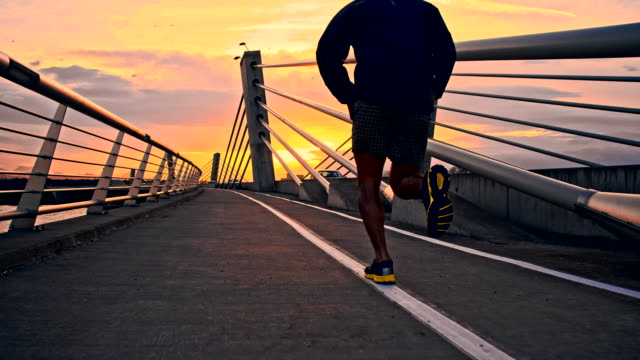 SLO MO Jogging Across A Bridge At Dusk video