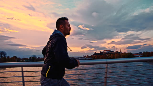 SLO MO Jogging Across The Bridge At Sunset video