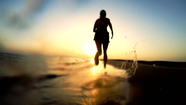 Jogging after sunset. Beach holiday Young woman jogging at sea shore. Red sunset effortless stock videos & royalty-free footage
