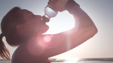 vídeos de stock e filmes b-roll de jogging na praia - bebida
