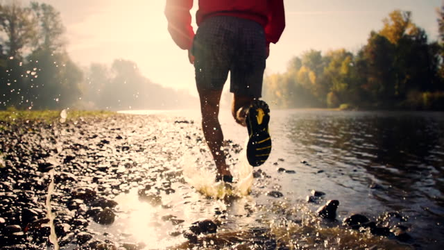 HD SUPER SLOW-MO: Jogging By The River HD1080p: SUPER SLOW MOTION shot of a man splashing water while jogging along the river at sunset. Crane shot. healthy lifestyle stock videos & royalty-free footage