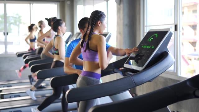 vídeos de stock e filmes b-roll de jogging cardio on machine,group young people doing exercises in gym - aparelho de musculação