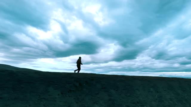 jogging in extreme terrain. crater lake - дикая местность стоковые видео и кадры b-roll