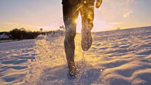 SLO MO Jogging In The Snow HD1080p: SLOW MOTION MEDIM Camera Stabilization shot of a man jogging across the snowy field at sunset. Time Warp. recreational pursuit stock videos & royalty-free footage