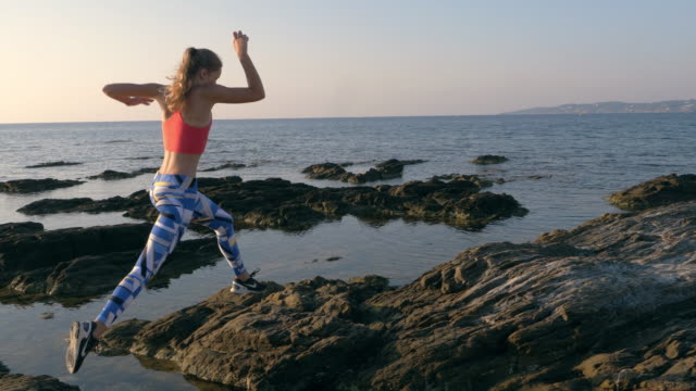 fare jogging su una costa rocciosa - termine sportivo video stock e b–roll