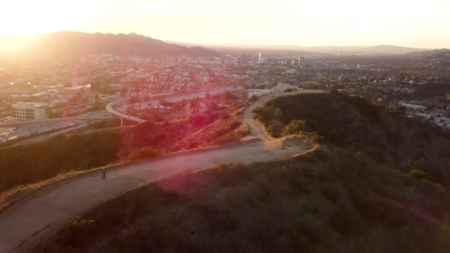 Jogging on Southern California Mountain Trail - Aerial Drone Shot This is a clip of an adult female jogger in black jogging on a fire road trail in the hillsides near the 210 and 2 freeway interchange. b roll stock videos & royalty-free footage