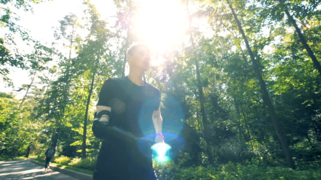 vídeos de stock e filmes b-roll de jogging training of a teenager with a prosthetic hand. futuristic human cyborg concept. - membro