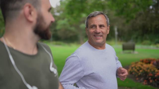 與兒子在公園慢跑 - 休閒器具 個影片檔及 b 捲影像