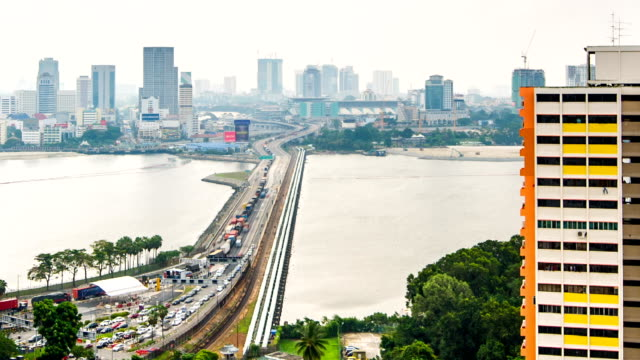 Johor–Singapore Causeway in Timelapse Johor–Singapore Causeway, linking the city of Johor Bahru in Malaysia across the Straits of Johor to the town of Woodlands in Singapore, it carries 60,000 vehicles on a typical day. Timelapse photography. johor bahru stock videos & royalty-free footage