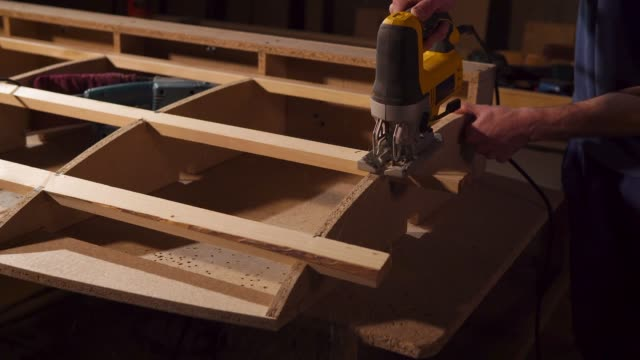 Joiner is cutting parts of wooden beams, installing in a frame of furniture video