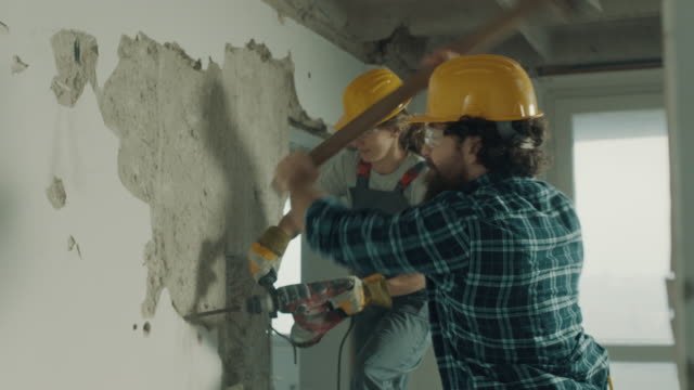 Joint forces! Male and female construction worker demolishing wall together renovation stock videos & royalty-free footage