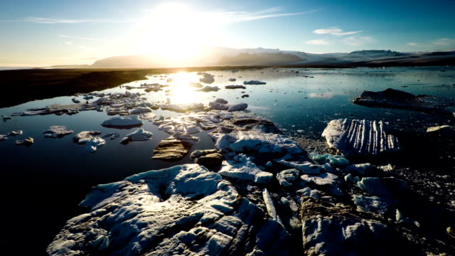 AERIAL: Jokulsarlon glacier lake at sunset, Iceland Flight over floating icebergs in Fjallsarlon glacier lake at sunset. South Iceland.Close to Jokulsarlon lagoon. Could be used as a theme for global warming and climate change. polar climate stock videos & royalty-free footage