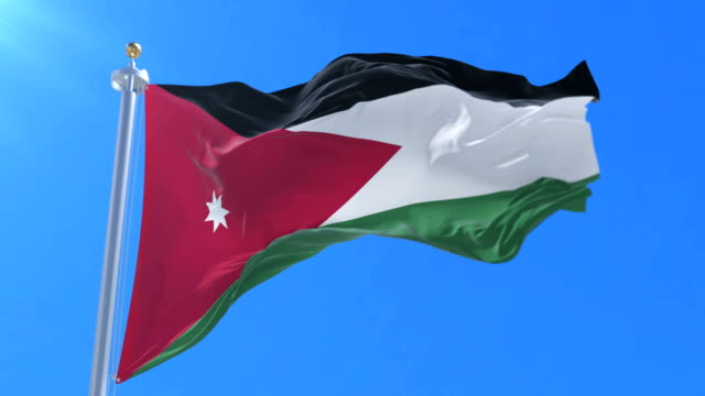 Jordanian flag waving at wind with blue sky in slow, loop