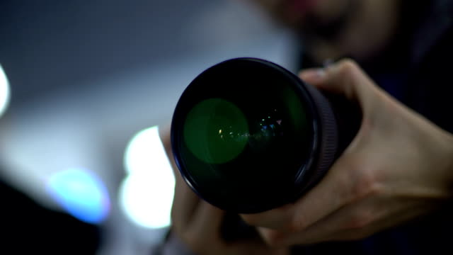 Journalist holding camera taking shots for report, paparazzi spying on celebrity