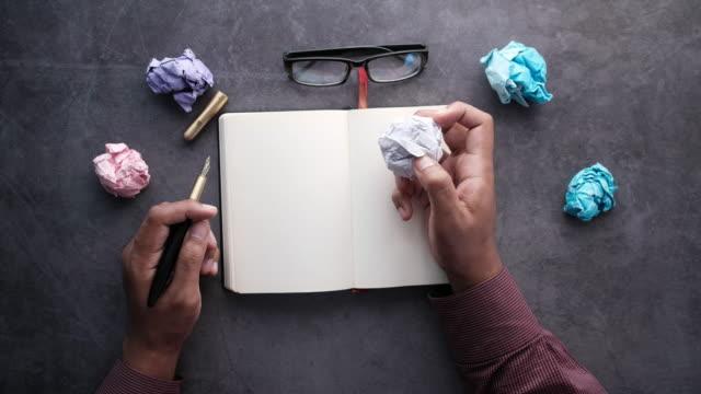 vídeos de stock e filmes b-roll de journalist's table with notebook, crumpled paper on black background - amarrotado