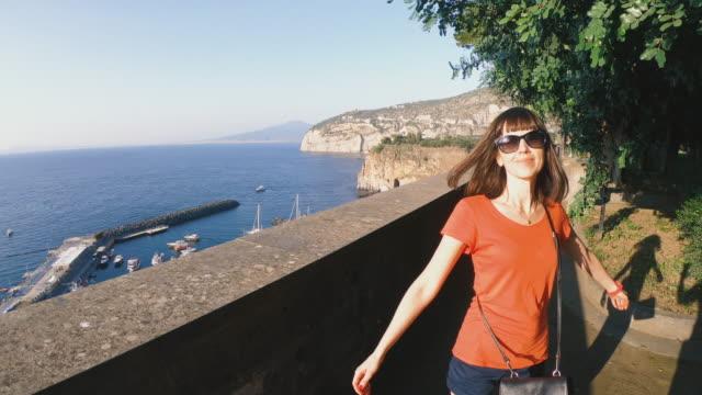 journey. a girl walks along the promenade of sorrento. italy. - pantaloncini video stock e b–roll