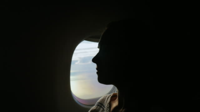vídeos de stock e filmes b-roll de journey in an airplane. silhouette of a young woman on the airplane window - amizade feminina