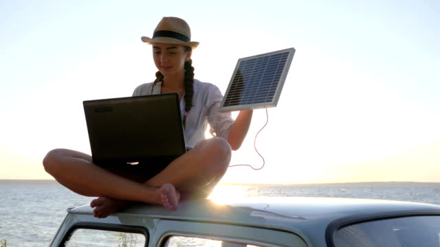 journey, young woman using powered solar cell for computer on background beach sitting on vintage car in sunlight video