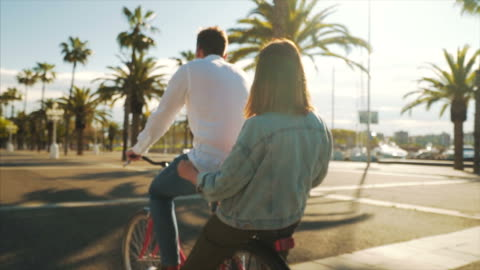 Joy can be found in small things. Happy young couple on bicycles enjoying beautiful moments together. They are visiting Barcelona. Slow motion scene. enjoyment stock videos & royalty-free footage
