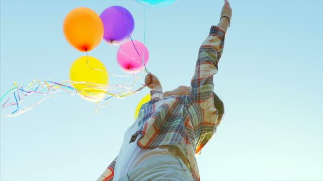 vídeos de stock e filmes b-roll de joy moments in slow motion. - mulher balões
