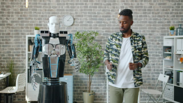 Joyful African American man dancing with human-like robot in office having fun video