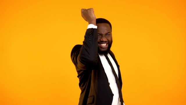 Joyful afro-american businessman celebrating successful stock market deal income Joyful afro-american businessman celebrating successful stock market deal income salesman stock videos & royalty-free footage