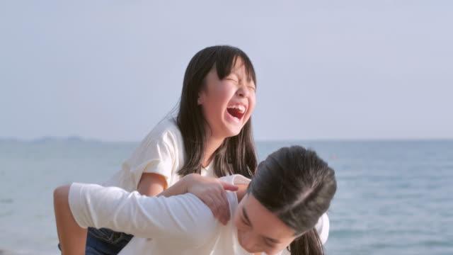 楽しいアジアの女の赤ちゃんは砂浜で海のサーフィンの端に沿って楽しんで母親の背中に乗る。子供と夏休みに活発な親や人々の屋外活動。幸せな家族の休日, 家族, ライフスタイル, 人々, � - 母娘 笑顔 日本人点の映像素材/bロール