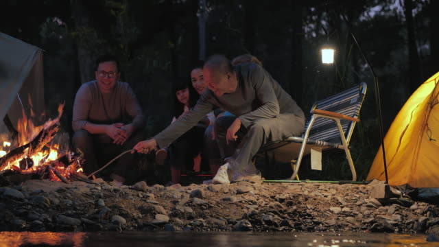 Joyful asian large family enjoying in camping at night near campfire on forest.Family,Lifestyle,People,Elderly,Vacations,Relationship,Holiday,Retirement,Healthycare and medicine concept.South East and East Asia: Generational Family,Bonfire