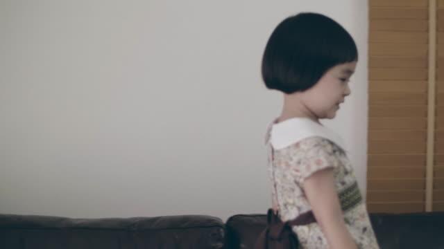 Joyful baby girl fashion model catwalk posing in living room video