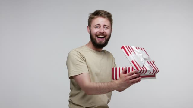 Joyful bearded man slowly opening gift box, unwrapping birthday surprise and expressing great happiness amazement Joyful bearded man slowly opening gift box, unwrapping birthday surprise and expressing great happiness amazement, satisfied with best present bonus. indoor studio shot isolated on gray background unpacking stock videos & royalty-free footage
