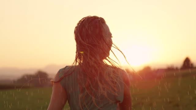 vídeos y material grabado en eventos de stock de close up alegre chica rubia disfruta su noche en el campo bailando bajo la lluvia - lluvia