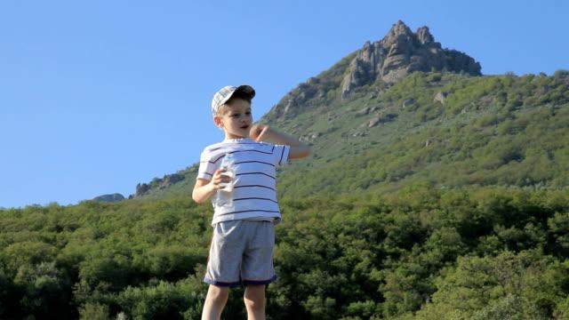 喜びの少年からのボトル入り飲料水に山を散策 - 男の子点の映像素材/bロール