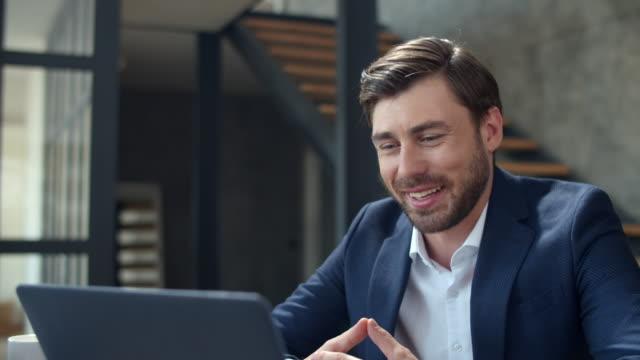 vidéos et rushes de homme d'affaires joyeux faisant l'appel web sur l'appareil-photo d'ordinateur portatif. téléphone de conférence de type effectuant - conférence en ligne
