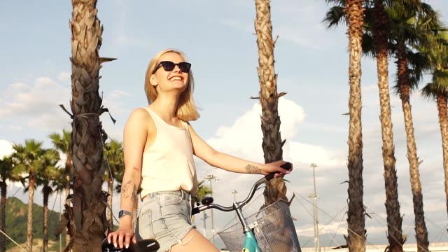 Joyful caucasian woman riding bicycle in park having fun in summer afternoon